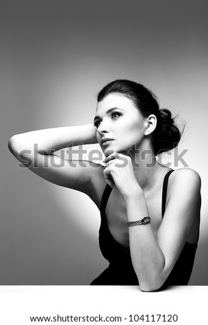 Black and white portrait of fashion woman in black dress on natural background