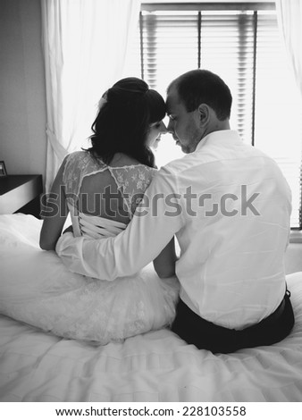 Black and white portrait of groom sitting on bed and hugging bride  - stock photo
