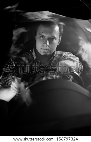 Black and white portrait of handsome driver holding steering wheel - stock photo