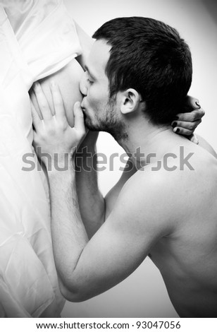 Black and white portrait of handsome man kissing his pregnant wife belly