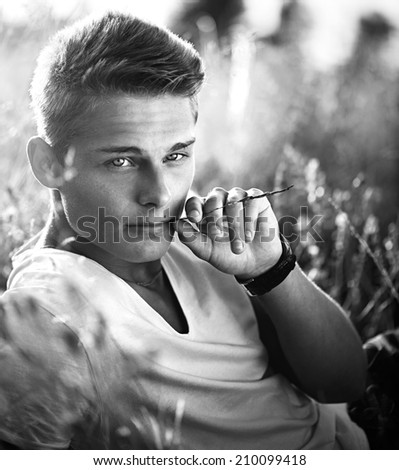 Black and White portrait of Handsome teenage guy lying on the field. Young man enjoying nature outdoors. Looking an camera and smiling. - stock photo