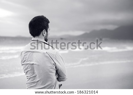 Black and white portrait of handsome young Caucasian man walking alone on the beach - stock photo