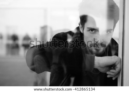 Black and white portrait of handsome young man with beard looking at camera while leaning on glass beyond the window - stock photo