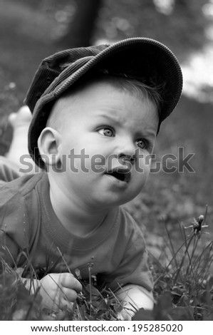Black and white portrait of happy eight month old baby boy in hat , lying or crawling on the grass - stock photo