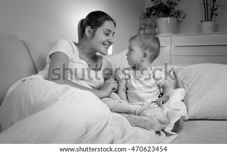Black and white portrait of happy mother talking with her baby in bed at late evening