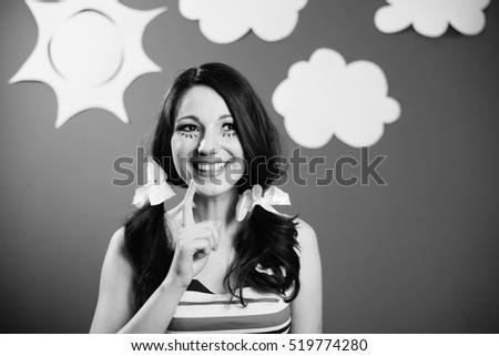 Black and white portrait of happy smiling pretty young woman over paper sky with white clouds copy space background
