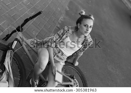 Black and White. Portrait of happy young bicyclist woman reading book in city