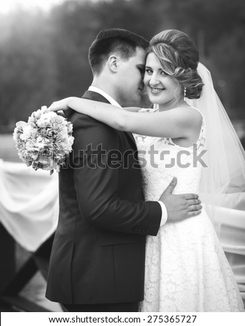 Black and white portrait of hugging and laughing bride and groom at park