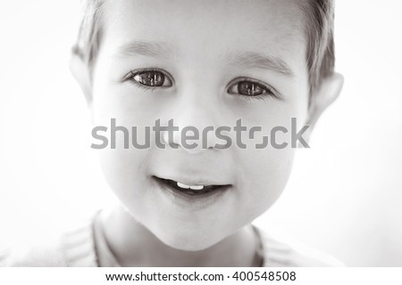 Black and white portrait of laughing boy on gray background. - stock photo
