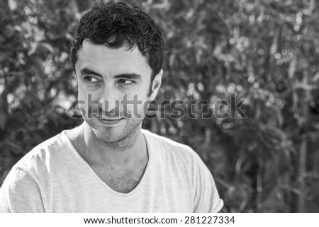 Black and white portrait of man of about thirty-five yers old, posing smiling to the camera. - stock photo