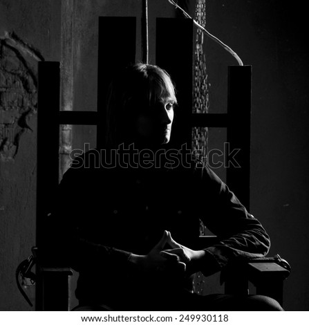 Black and white portrait of man on electric chair  . Dramatic studio lighting - stock photo