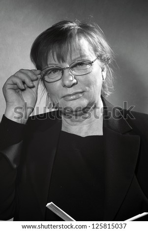 black and white portrait of middle aged woman in eyeglasses with book