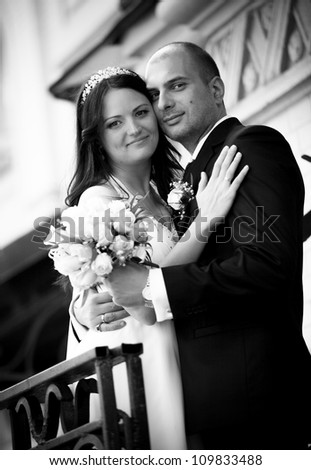 Black and white portrait of newly married couple posing near building
