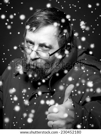 Black and white portrait of senior man in glasses showing yes sign. Christmas and holidays concept