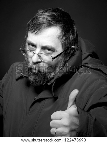 Black and white portrait of senior man in glasses showing yes sign over dark background - stock photo