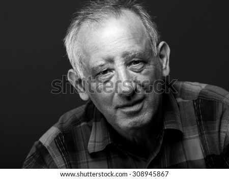 Black and white portrait of senior man looking at camera.