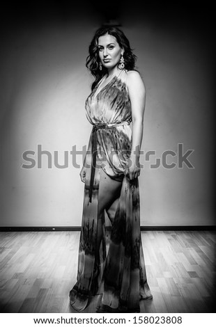 Black and white portrait of sexy brunette in long dress