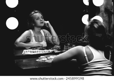 Black and white portrait of sexy woman painting lips at mirror with bulbs - stock photo