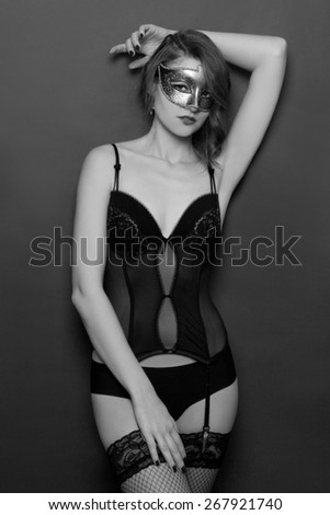 black and white portrait of sexy woman posing in lingerie and mask - stock photo