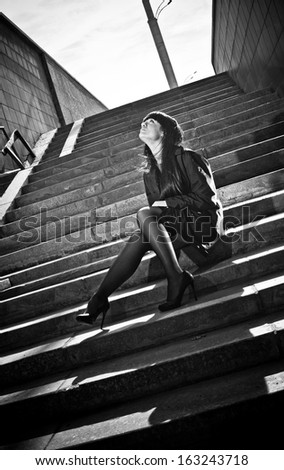 Black and white portrait of sexy woman sitting on stairs on street - stock photo