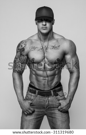 Black and white portrait of shirtless bodybuilder with tattooes isolated on grey background.
