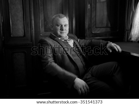 Black and white portrait of stylish man in retro suit sitting in armchair at office