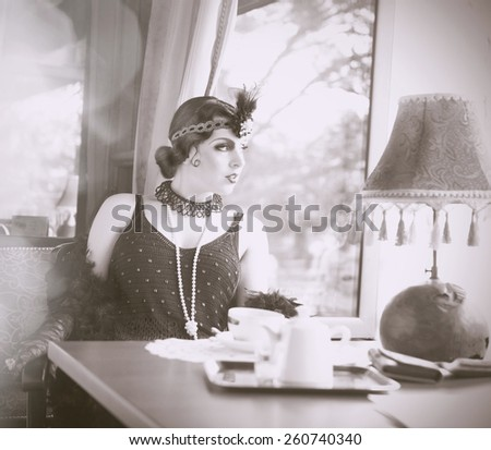 Black and White Portrait of The Beautiful Retro woman Drinking Tea in the Cafe in Black Lace and Accessories in Style 1920s - 1930s  - stock photo