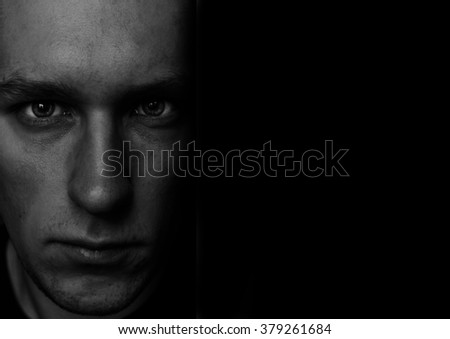 Black and white portrait of the young man in low key - stock photo