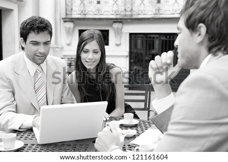 Black and white portrait of three business people sharing a table at a coffee shop terrace, having a meeting and talking while using technology in the financial city district. - stock photo
