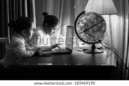 Black and white portrait of two girls typing e-mail on laptop at night - stock photo