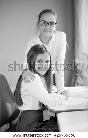 Black and white portrait of two happy schoolgirls posing at home - stock photo