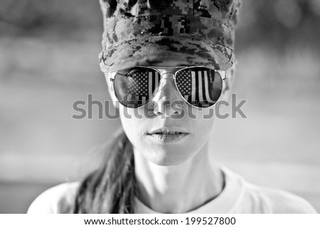 Black and white portrait of us army woman with american flag reflection in the sunglasses - stock photo