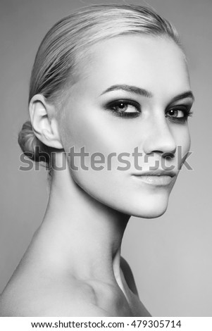 Black and white portrait of young beautiful girl with stylish smoky eye make-up and hair bun