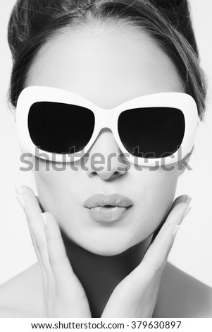 Black and white portrait of young beautiful woman in vintage sunglasses
