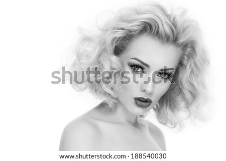 Black and white portrait of young beautiful woman with blond curly hair and false eyelashes over white background - stock photo