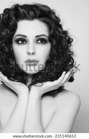 Black and white portrait of young beautiful woman with long healthy curly hair