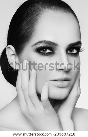 Black and white portrait of young beautiful woman with smoky eyes and hair bun - stock photo