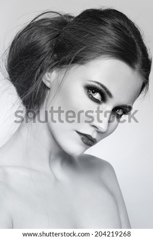 Black and white portrait of young beautiful woman with stylish hair bun - stock photo