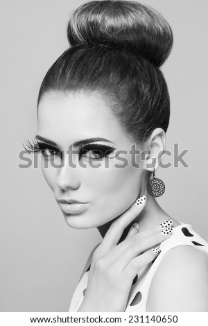 Black and white portrait of young beautiful woman with stylish make-up, hair bun and fancy polka dot manicure - stock photo