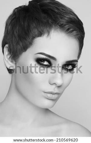 Black and white portrait of young beautiful woman with stylish short haircut and smoky eyes - stock photo