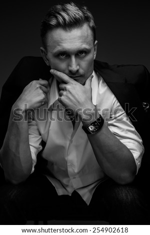 Black and white portrait of young business man in a suit on dark black background. - stock photo