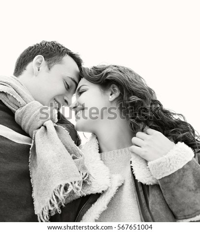 Black and white portrait of young couple on winter holiday against sky, smiling joyful with heads together, recreation lifestyle outdoors. Seasonal travel. Boyfriend and girlfriend loving romance.