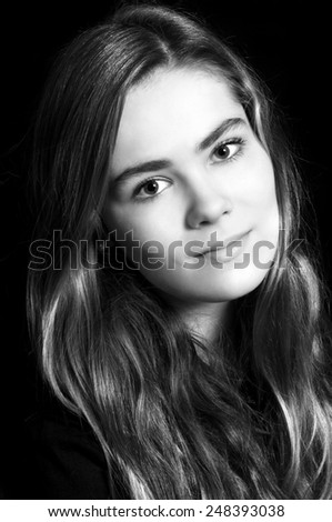 black and white portrait of young girl isolated against a black background  - stock photo