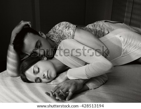 Black and white portrait of young lovers couple laying together hugging in bed home interior, sharing affection, indoors. Relationships lifestyle, bedroom passion. Boyfriend and girlfriend closeness. - stock photo