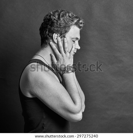Black and white portrait of young man holding his head to calm a headache on a gray background - stock photo