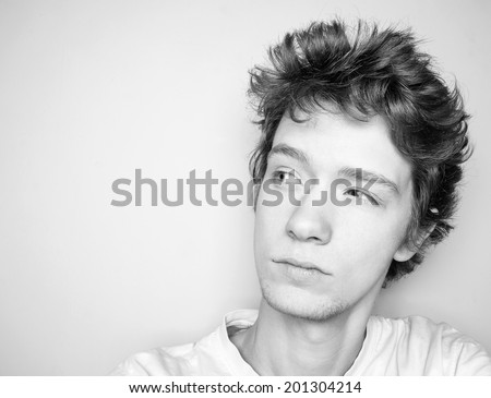Black and white portrait of young man thinking and looking away left.