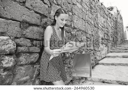 Black and white portrait of young tourist woman visiting a destination city with old textured stone wall in a street with steps, using a map, sightseeing on holiday. Travel vacation, outdoors. - stock photo