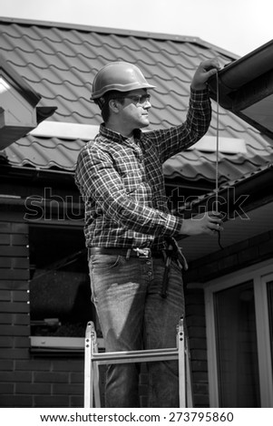 Black and white portrait of young worker repairing house roof  - stock photo