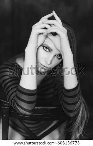 Black and white portraits of a beautiful girl on a dark background long beautiful hair