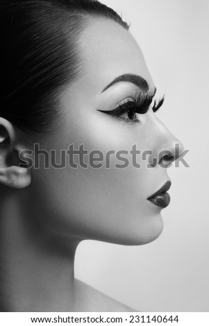 Black and white profile portrait of young beautiful girl with long false eyelashes - stock photo